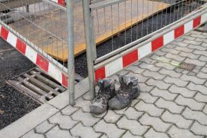 Baustellenabsperrung und Arbeitsschuhe